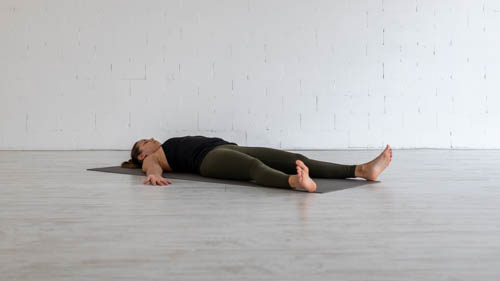 The yoga teacher rests in the Corpse pose.