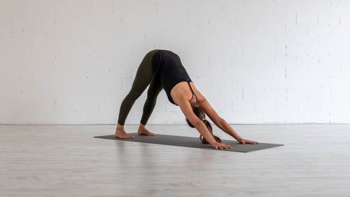 The yoga teacher holds the Downward-facing dog pose.