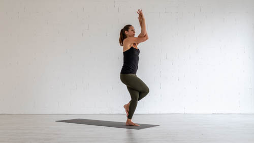 The yoga teacher holds the Eagle pose.