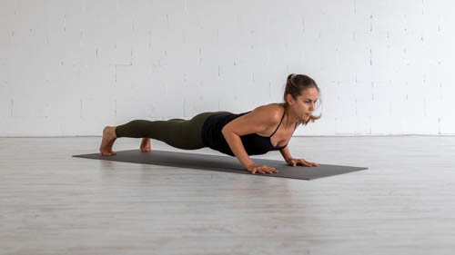The yoga teacher holds the Low plank pose.