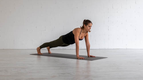 The yoga teacher holds the Plank pose.