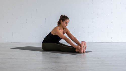 The yoga teacher holds the Seated forward bend pose.