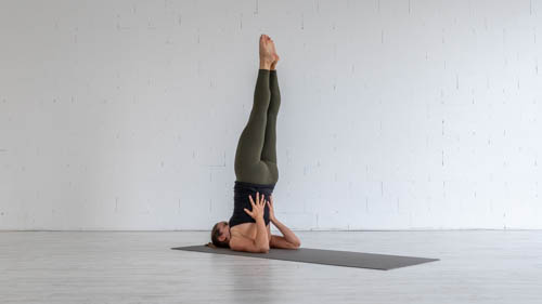 The yoga teacher holds the Shoulder stand pose.
