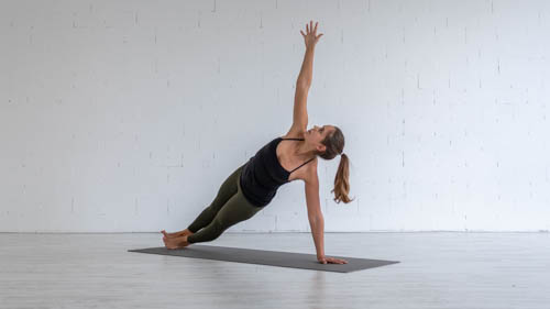 The yoga teacher holds the Side plank pose.