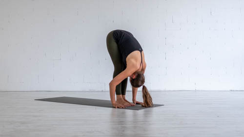 The yoga teacher holds the Standing forward bend pose.
