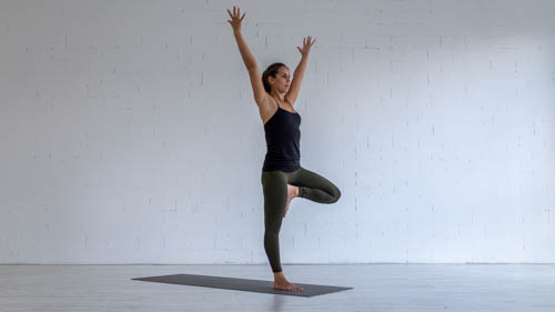 The yoga teacher holds the Tree pose.