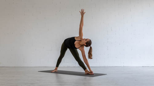 The yoga teacher holds the Triangle pose.