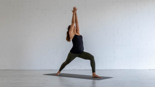 The yoga teacher holds the Warrior 1 pose.