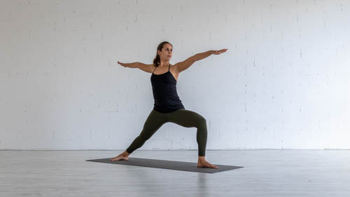 The yoga teacher holds the Warrior 2 pose.