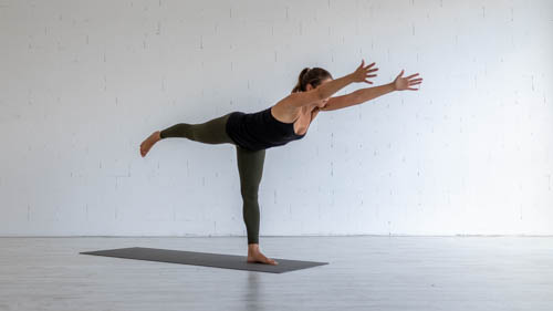 The yoga teacher holds the Warrior 3 pose.